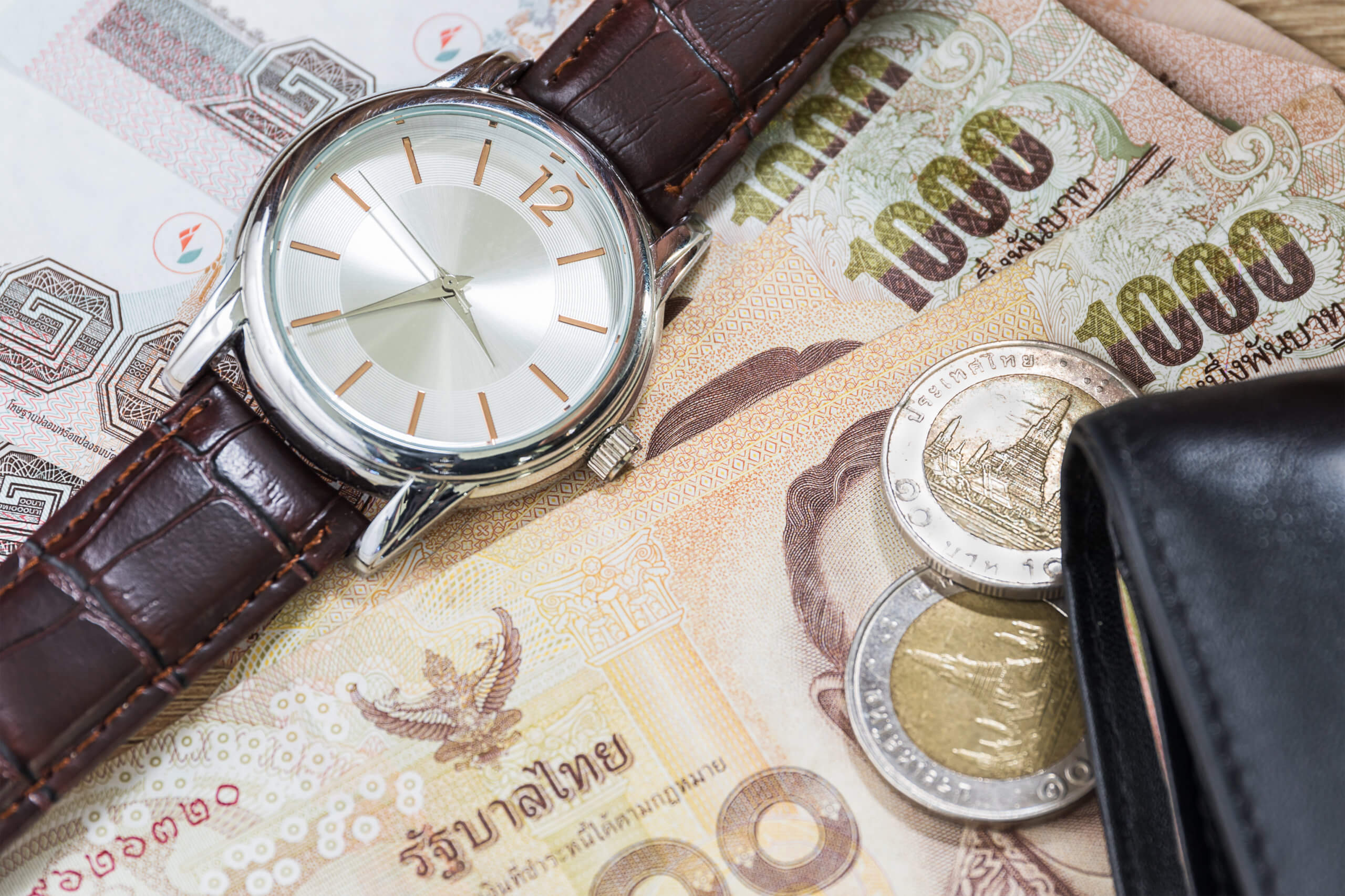 Watch and wallet on banknote
